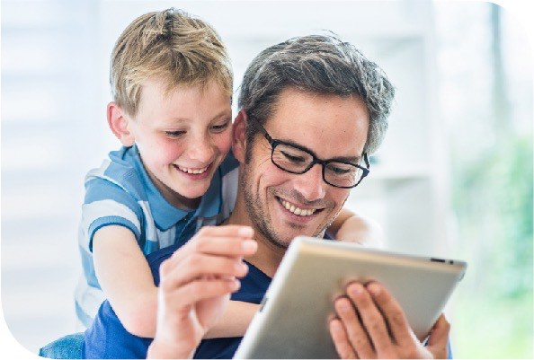 Man using tablet with young child looking over his shoulder