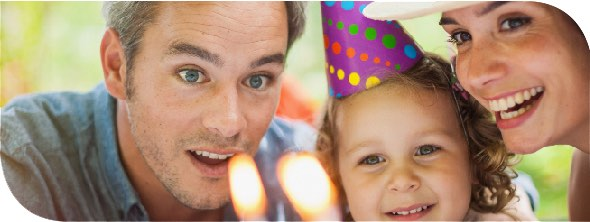 Two parents standing on either side of their toddler wearing a birthday party hat.