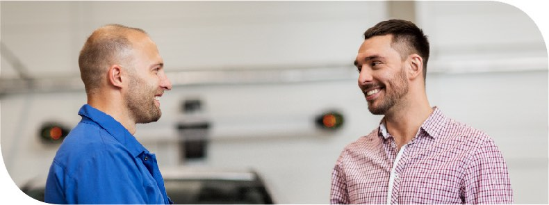Auto-mechanic speaking with customer. Both are smiling.